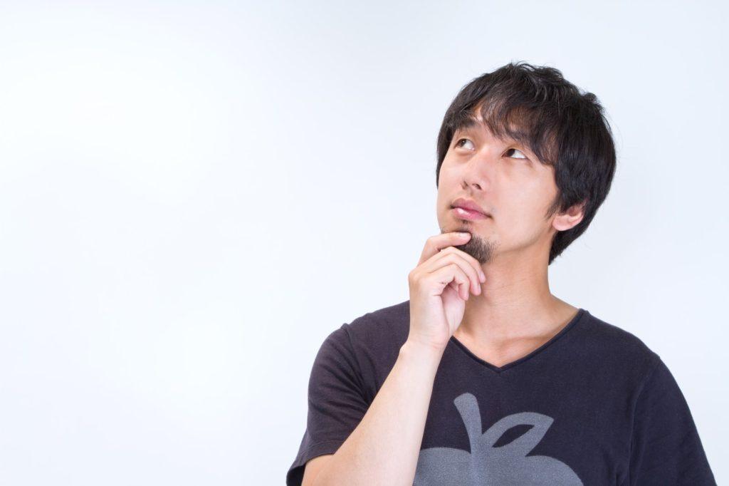 ヒゲをいじり上を見上げる男性 [モデル:大川竜弥]